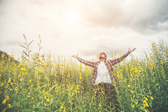 Handsome hipster man standing raising hands in the air in a yellow flower field.